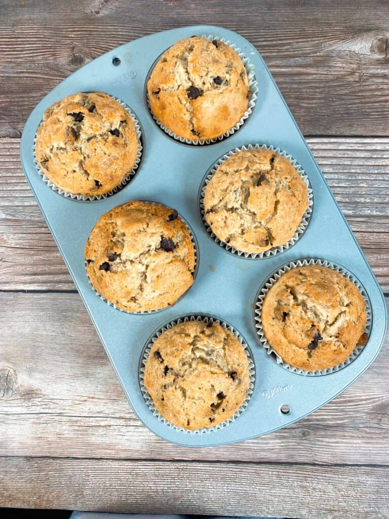 image looking down on a tray of baked jumbo banana muffins with tall domes rising way over the muffin pan. Muffin pan sits on a wooden background.