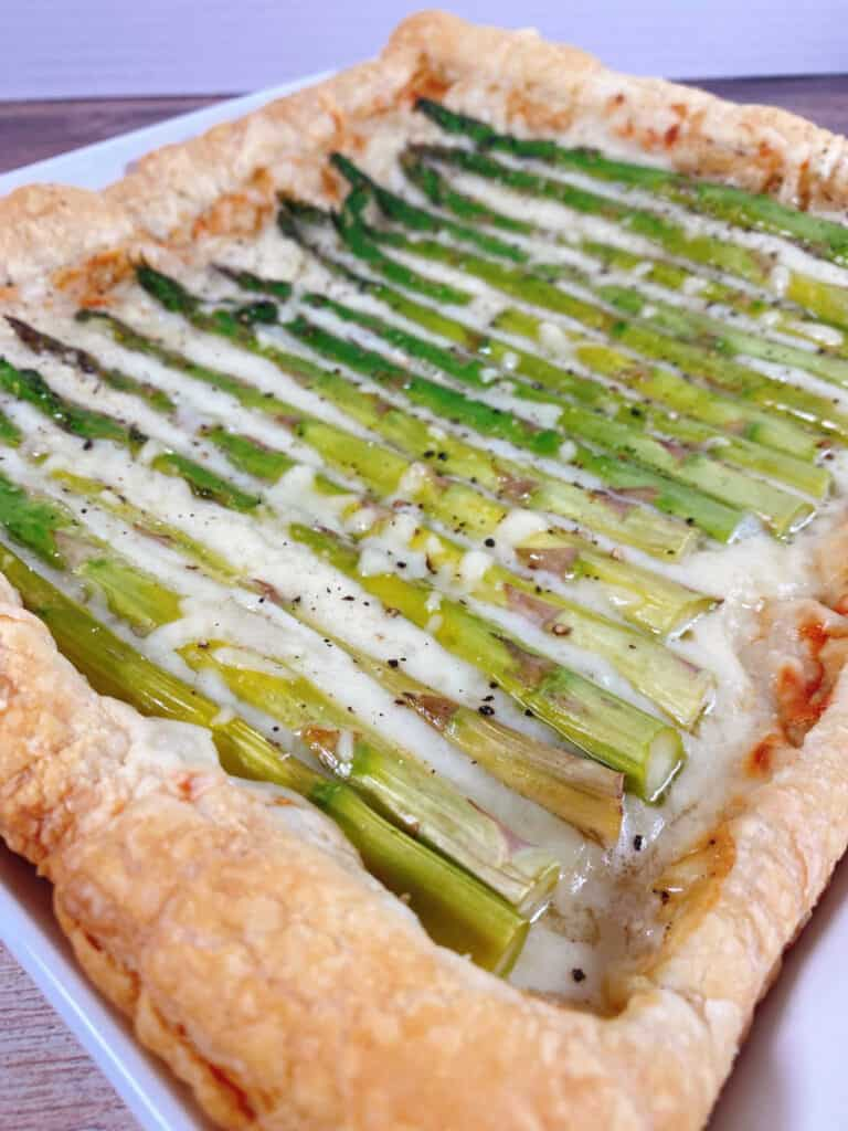 Close up image of asparagus and gruyere tart. Puff pastry is layered with a sauce and shredded gruyere cheese and topped with fresh asparagus spears, then baked to golden perfection.