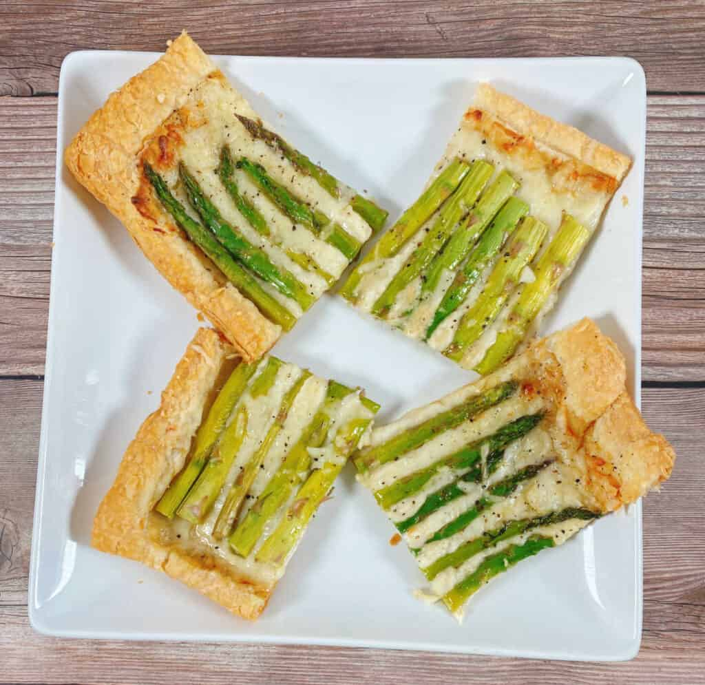 slices of asparagus and gruyere tart sit on a white square platter on a wooden background. There are 4 squares of the tart, two showing the tops of the asparagus and two showing the bottom of the asparagus spears.
