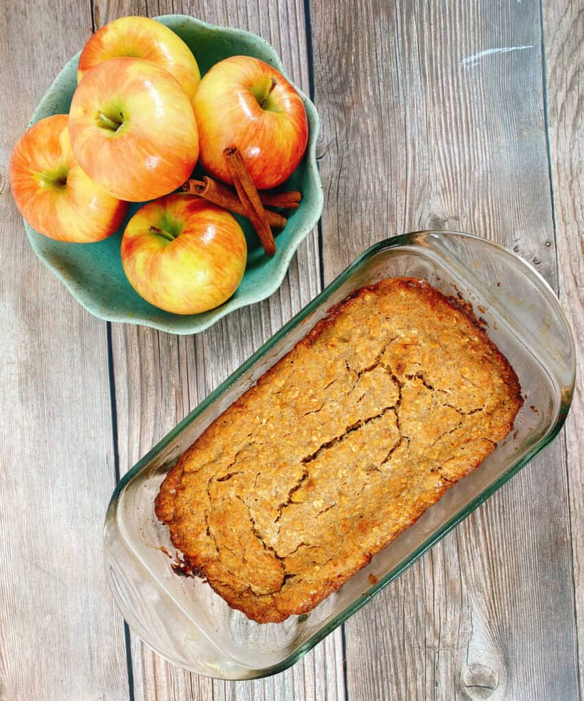 On a wooden background sits a bowl of honeycrisp apples and cinnamon sticks in a light green scalloped edge bowl. Below that sits the banana applesauce oatmeal bread, baked in a glass loaf pan. The top of the bread is cracked and golden brown.