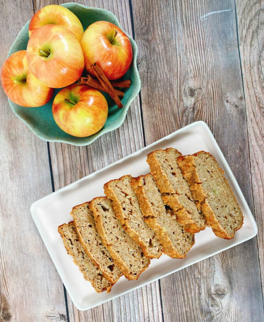 On a wooden background sits the banana applesauce oatmeal bread cut into slices on a rectangle white platter. There is also a bowl of honeycrisp apples and a few cinnamon sticks in a green bowl with scalloped edges.