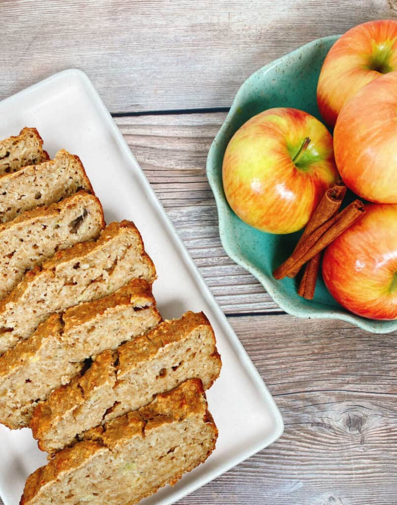 Close up image of the banana applesauce oatmeal bread. Slices of bread are layered on a white, rectangle shaped platter. Opposite the bread sits a light green bowl with scalloped edges. In the bowl are stacked honeycrisp apples and whole cinnamon sticks.