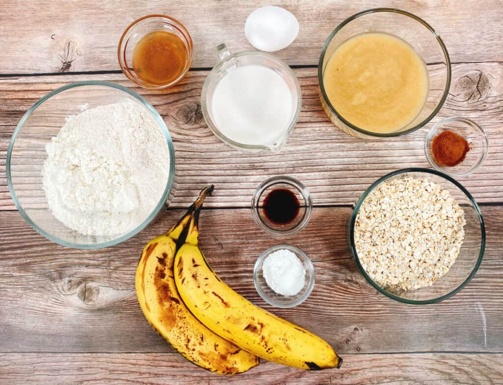 The ingredients for banana applesauce oatmeal bread sit on a wooden background. From left to right: all purpose flour, honey, bananas, almond milk, egg, vanilla, baking soda, applesauce, cinnamon and old fashioned oats.