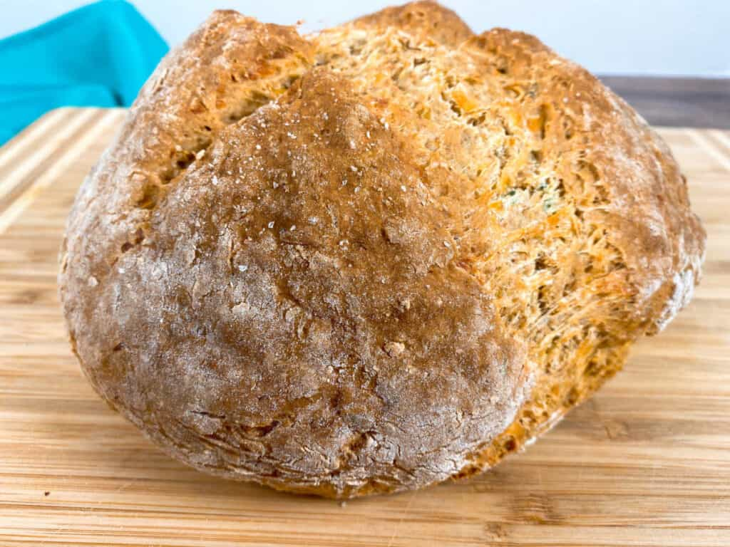 a freshly baked loaf of cheddar thyme irish soda bread sits on a wooden cutting board. the top of the bread is split, showing the baked goodness inside.