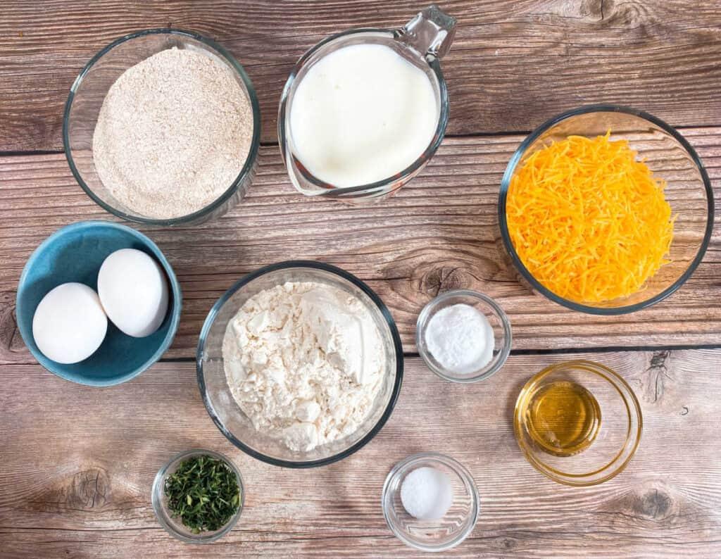 ingredients for cheddar thyme irish soda bread. All purpose flour, whole wheat flour, buttermilk, baking soda, honey, salt, eggs, shredded cheddar cheese and fresh thyme.