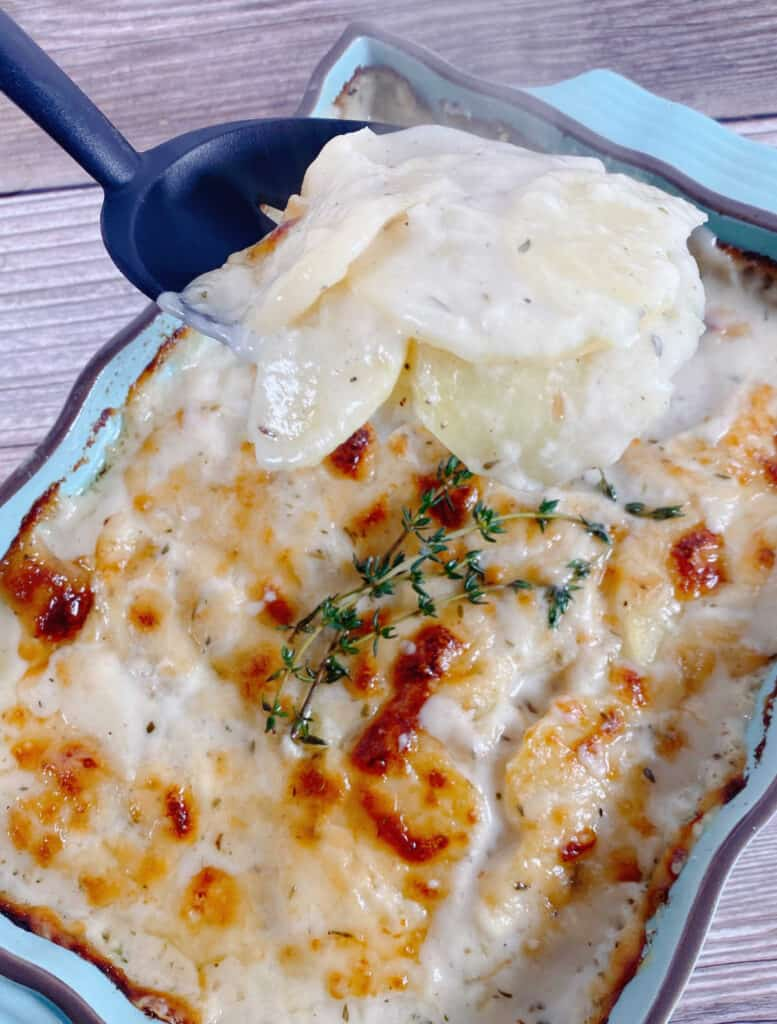 A slotted spoon lifts of a heaping spoonful of the easy cheesy scalloped potatoes from a light blue casserole dish. The dish sits on a wooden background. The remainder of the potatoes in the dish are lightly golden brown from the cheese and sprigs of fresh thyme sit on top.