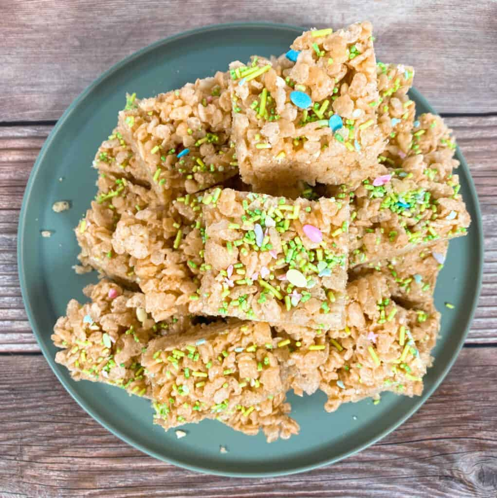 a stack of fruity easter rice krispie treats sits on a pale green plate on a wooden background. There're topping with easter sprinkles, in pastel colors. Some sprinkles are in the shape of an easter egg.