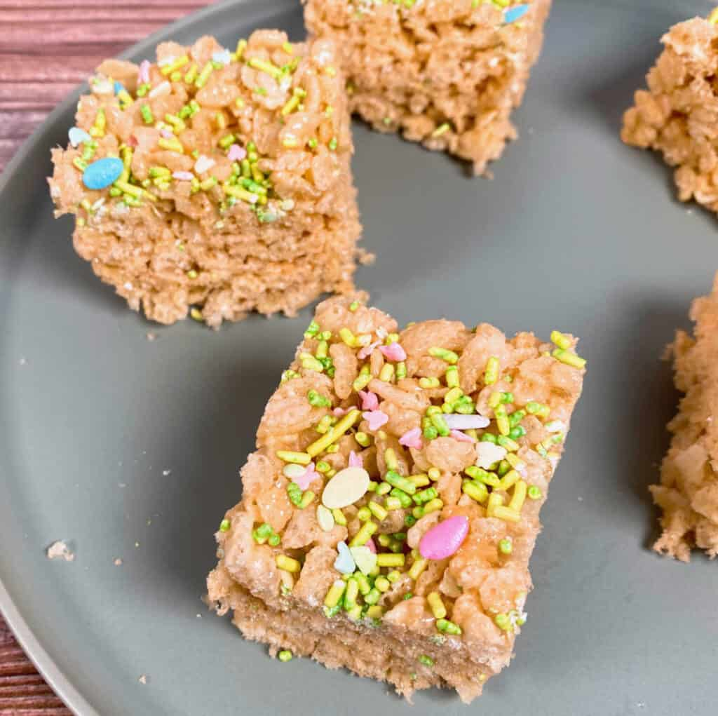 rice krispie treats made with fruit flavored marshmallows sit on a pale green plate and are topped with spring/easter sprinkles.