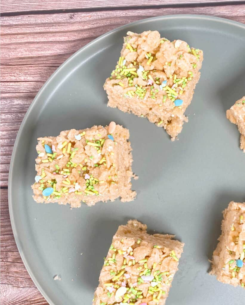 squares of fruity easter rice krispies sit on a pale green plate on a wooden background. the tops of the treats are covered in easter sprinkles, pastel in color and some are in the shape of easter eggs.