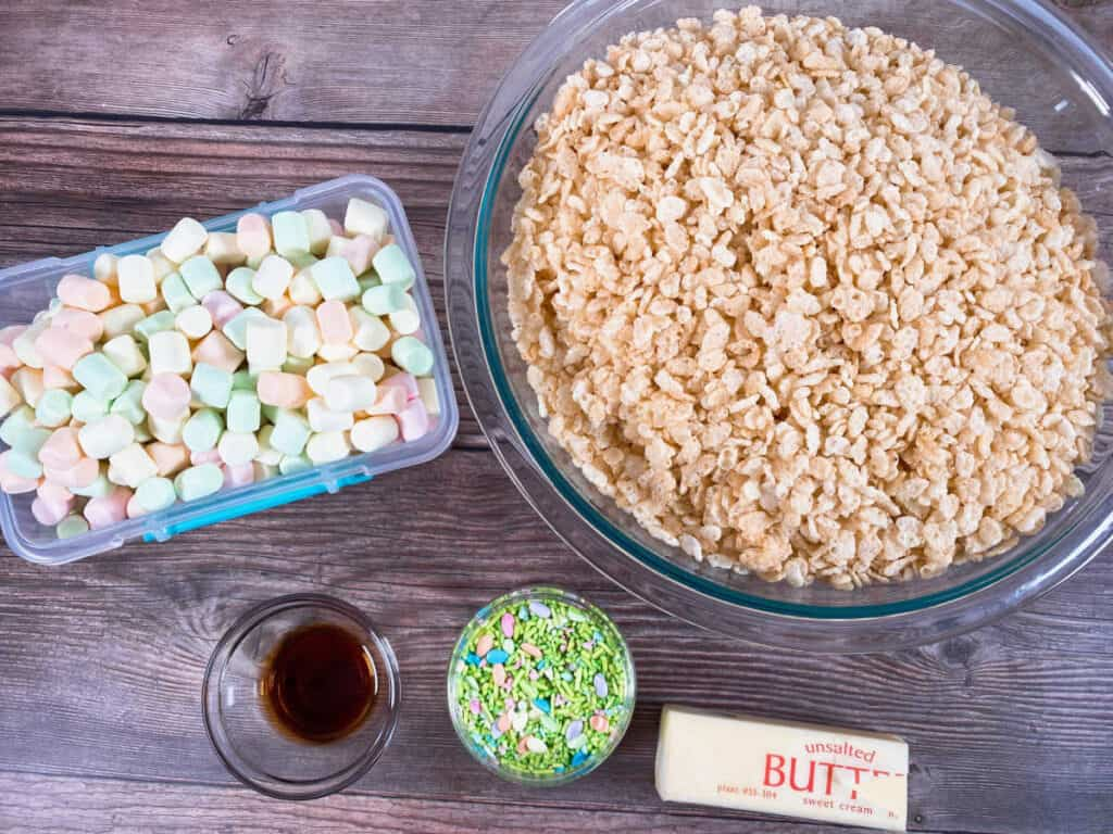 ingredients for fruity easter rice krispies sit on a wooden background. Fruity flavored marshmallows, rice krisipes cereal, vanilla extract, butte and easter sprinkles.