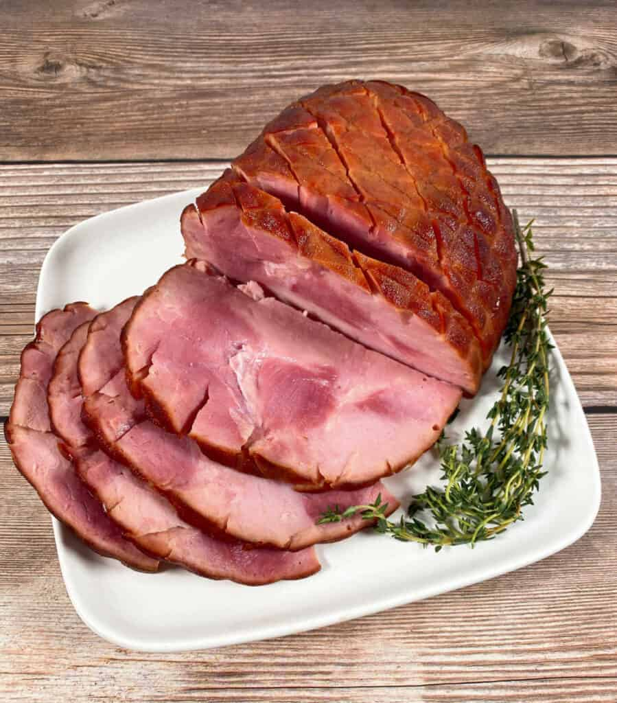 Slices of a honey bourbon baked ham sit on a white plate on a wooden background.