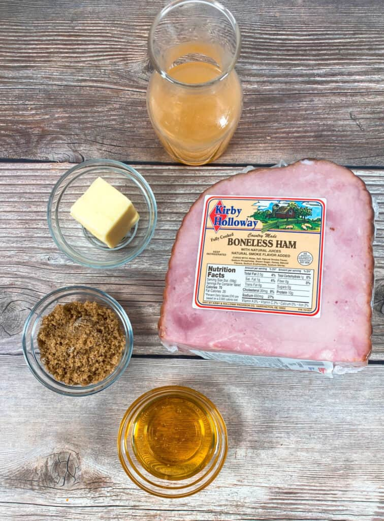 ingredients for honey bourbon baked ham sit on a wooden background. A ¼ ham, brown sugar, honey, butter and bourbon make up the glaze.