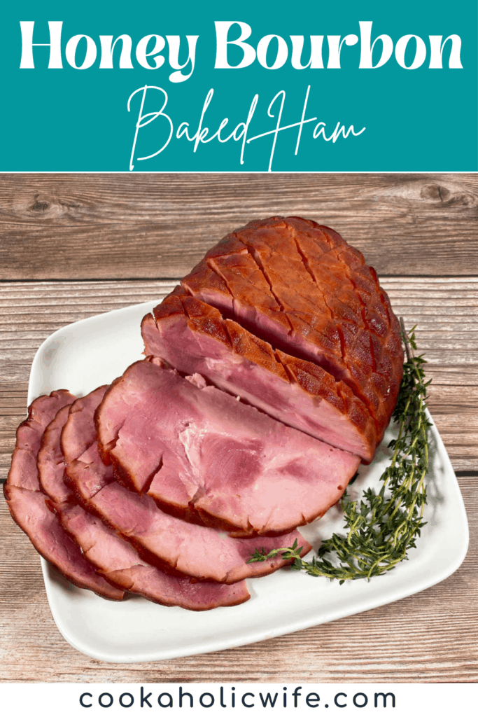 A partially sliced ham sits on a white plate on a wooden background. Next to the ham is fresh thyme. The ham is covered in a sweet glaze made with bourbon, brown sugar, honey and butter.