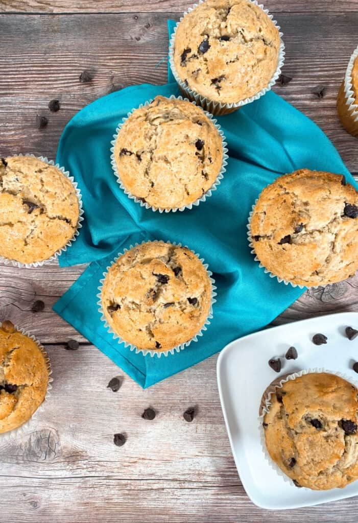Image looking down. On a wooden background sit jumbo chocolate chip muffins. Some are arranged on top of a teal napkin, another on a white plate. Some are cut off from fully being in the image. Chocolate chips are scattered around the muffins.