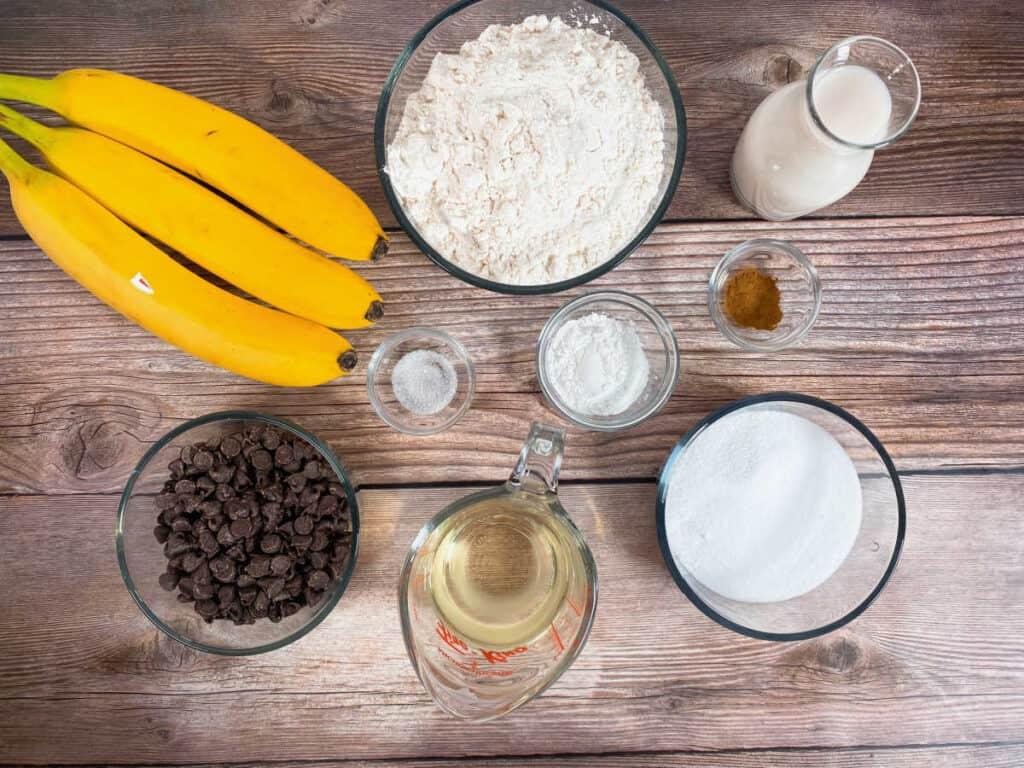 ingredients for jumbo banana chocolate  muffins: bananas, all purpose flour, milk, cinnamon, baking soda, salt, sugar, chocolate chips, vegetable oil. Not pictured: vanilla
