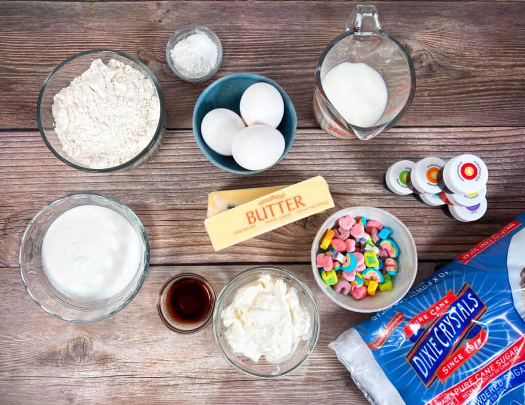 Ingredients for rainbow vanilla cupcakes sit on a wooden background. All purpose flour, sugar, butter, milk, sour cream, baking powder, vanilla and salt make up the cupcake ingredients. powdered sugar, food coloring and marshmallows from Lucky Charms cereal make up the frosting and decorations.