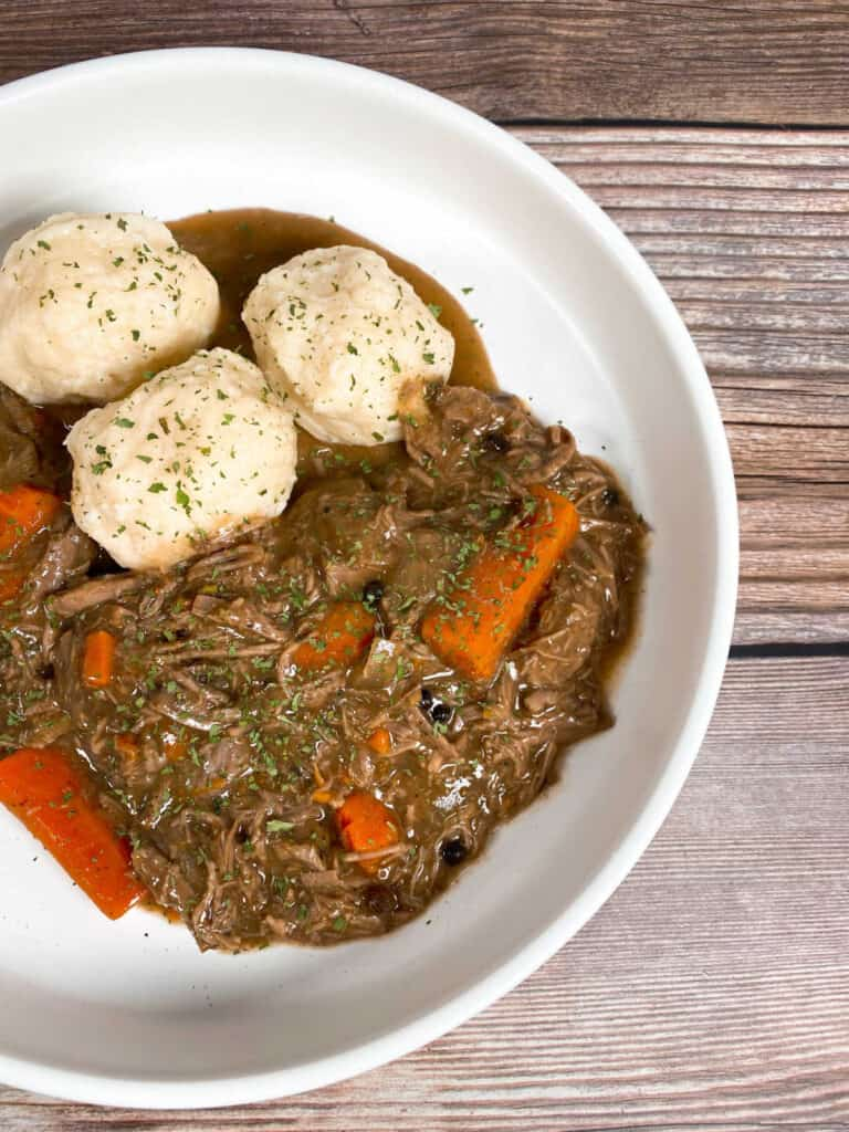 A shallow white bowl is full of sour beef and dumplings. The beef is marinated in vinegar and spices before being slow cooked with carrots and onions, then topped with  gravy made from gingersnap cookies. The potato dumplings are homemade and sprinkled with parsley.