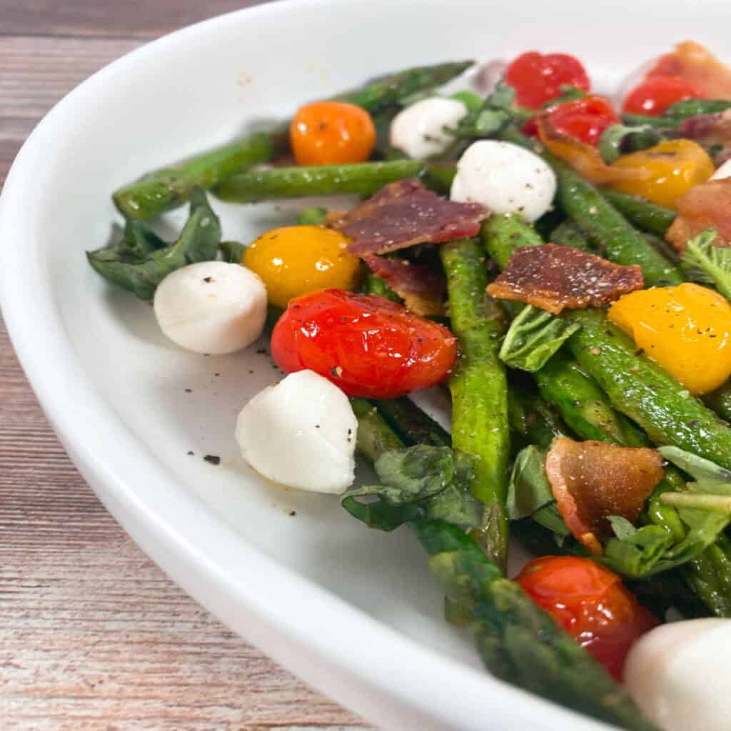 Close up side image of Asparagus Bacon Caprese Salad. Asparagus spears, grape tomatoes, crispy chopped bacon and mozzarella balls sit in the bowl, topped with chopped fresh basil and seasoned with salt and pepper.