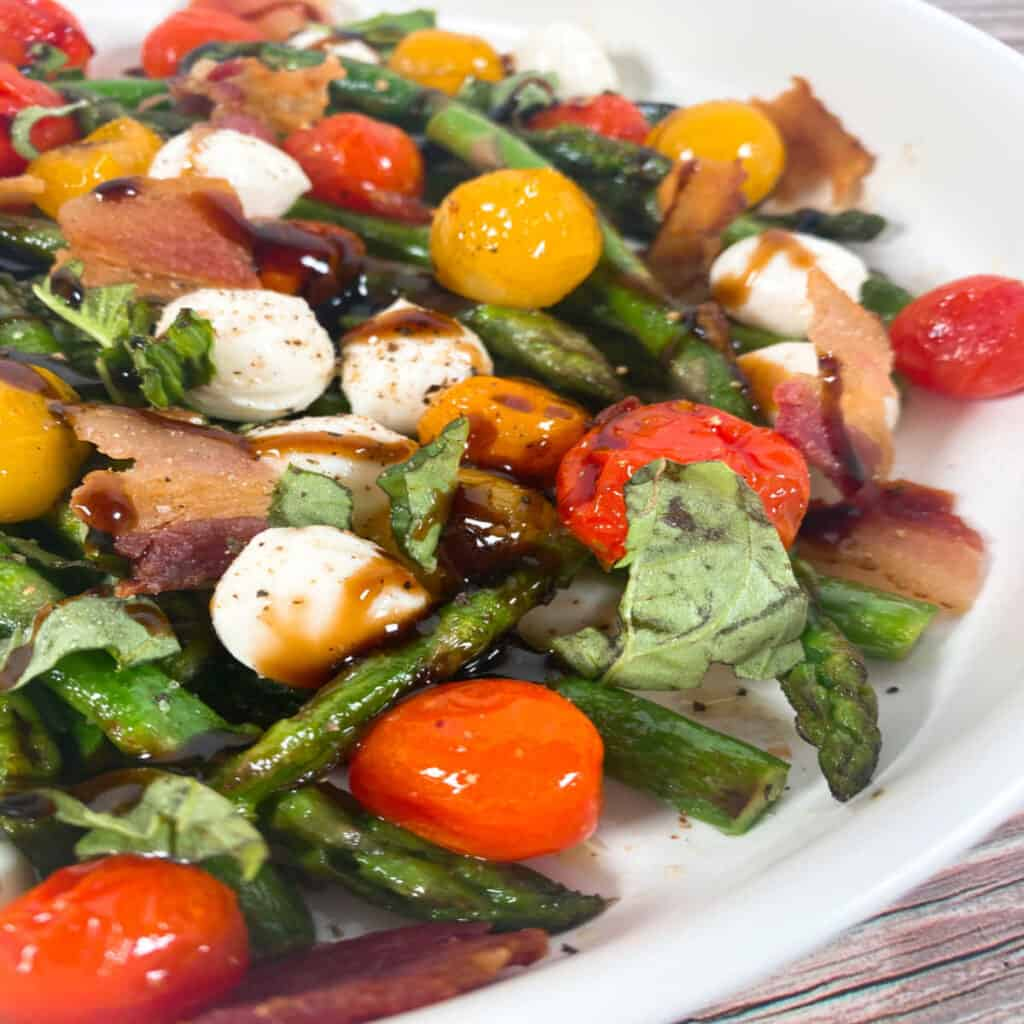 Close up image of Asparagus Bacon Caprese Salad. Spears of asparagus, grape tomatoes, mozzarella balls, chopped basil and crispy bacon are topped with balsamic glaze. The salad is in a white, shallow bowl.