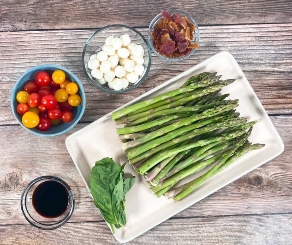 Ingredients for asparagus bacon caprese salad sit on a wooden background. Ingredients include balsamic glaze, grape tomatoes, mozzarella balls, chopped bacon, asparagus and fresh basil.