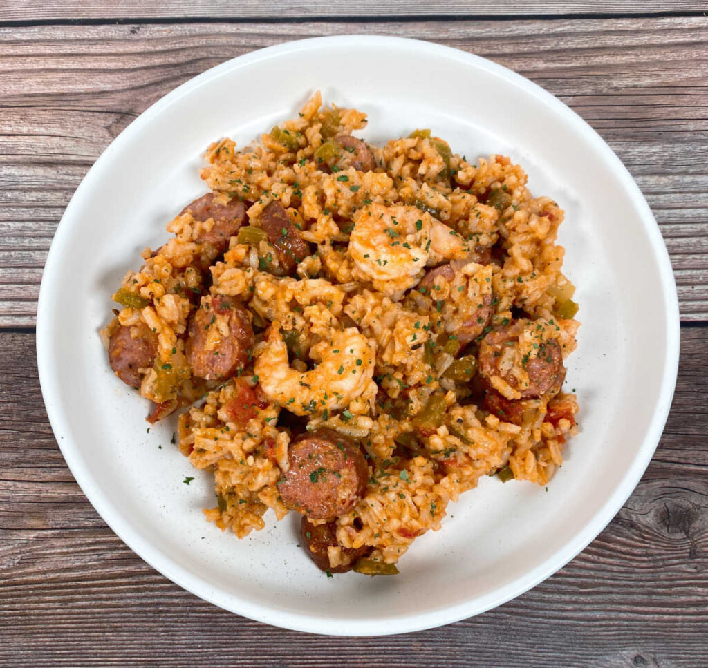 creole style jambalaya, made with chicken, sausage and shrimp sits in a shallow white bowl on a wooden background