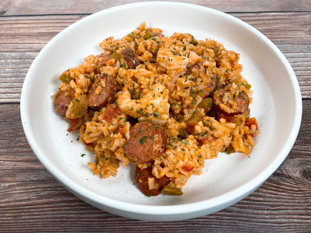 Top down image of the jambalaya, sitting in a shallow white bowl on a wooden background. The dish is sprinkled with parsley.