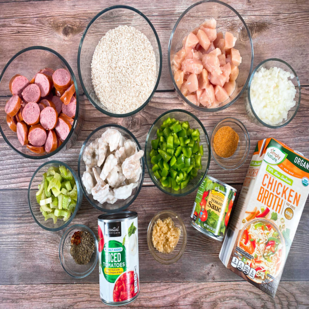 Ingredients for this recipe sit on a wooden background. Ingredients include bite sized pieces of chicken, sausage sliced into rounds, shrimp, green pepper, celery, onion, minced garlic, canned diced tomatoes, tomato sauce, chicken broth, Cajun seasoning, long grain white rice, dried thyme and oregano, crushed red pepper flakes, worcestershire sauce, salt and pepper.