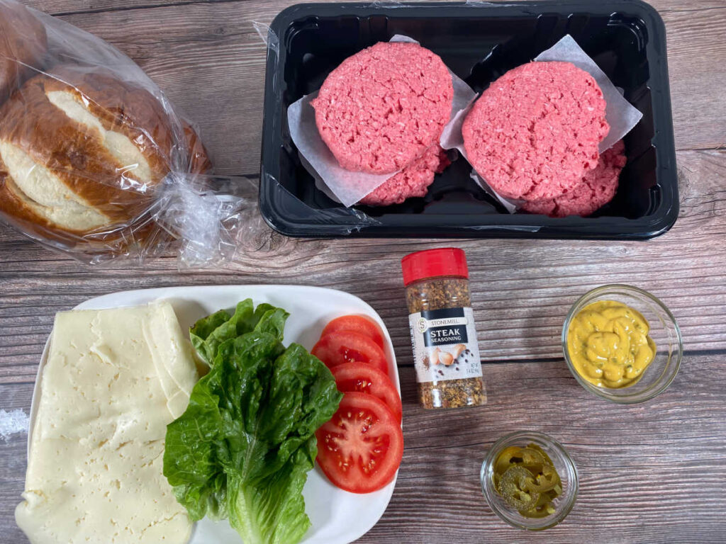 ingredients for the burger; burger patties, pretzel rolls, Havarti cheese, lettuce, tomato slices, grilling seasoning, jalapeno mustard and pickled jalapenos.