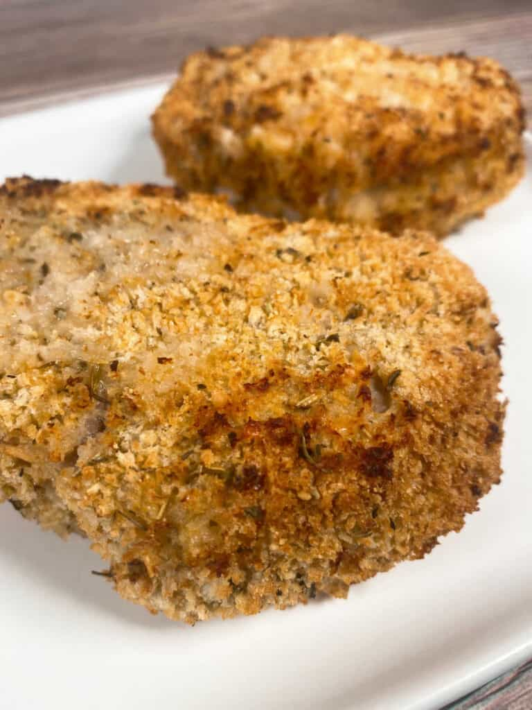 close up side image of the pork chop, showing the crispy coating made with Panko bread crumbs and Parmesan cheese.