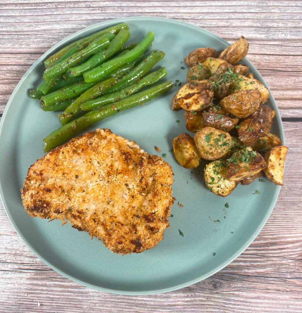 round green plate has the pork chop in the bottom portion of the plate, green beans in the top and potatoes on the side.