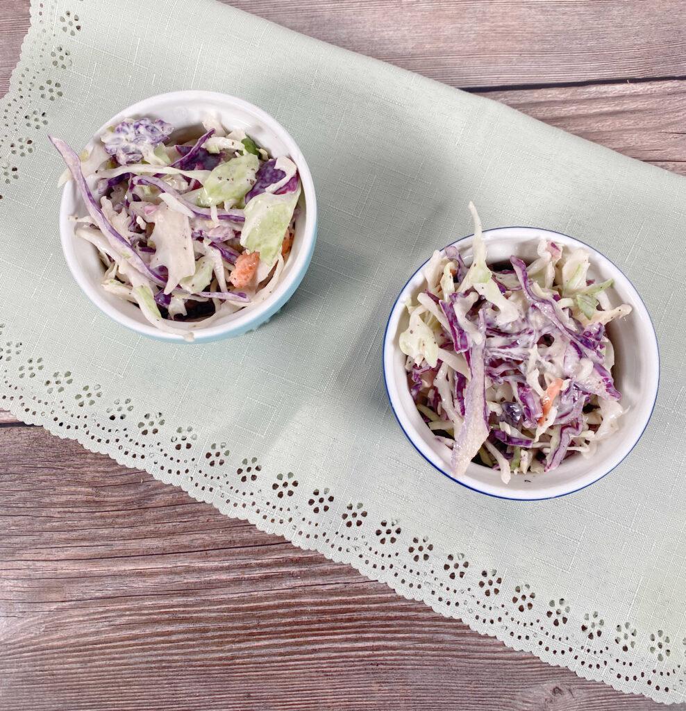 Prepared coleslaw sits in ramekins on a light green napkin,