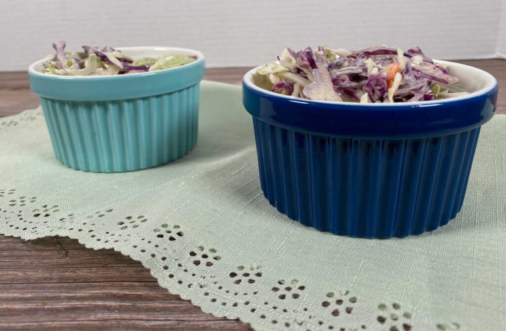 Prepared coleslaw sits in a turquoise and navy blue ramekin on a light green napkin.
