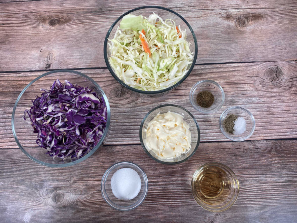 ingredients for this recipe sit in glass bowls on a wooden background. Ingredients include coleslaw mix, shredded red cabbage, mayo, sugar, apple cider vinegar, celery seed, salt and pepper.