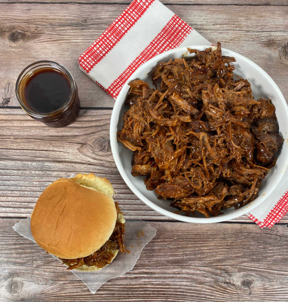 overhead view of a pulled pork sandwich sitting on a wooden background. Plate of additional pork sits in a white bowl on a checkered napkin and a mason jar of the bbq sauce sits in the background.