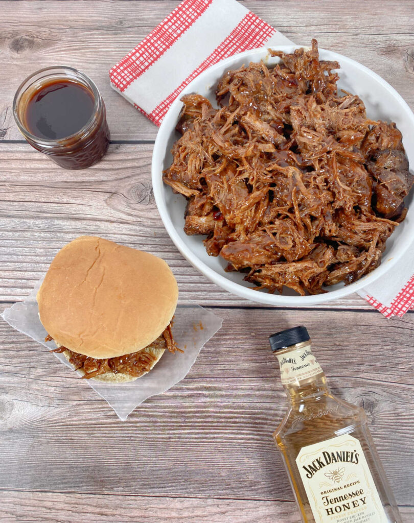 Overhead view of the pulled pork sandwich sitting on a square of wax paper. Additional pulled pork sits in a bowl, next to it the homemade bbq sauce and below it, the bottle of liquor used in the sauce.