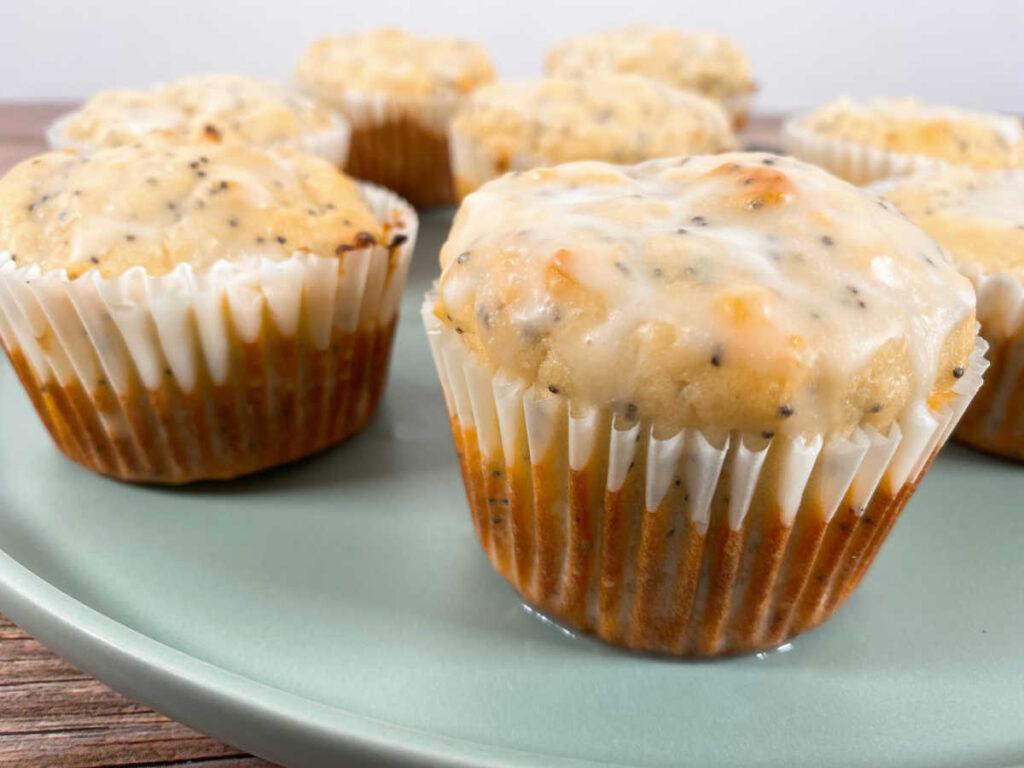 glazed lemon poppy seed muffins sit on a light green plate.