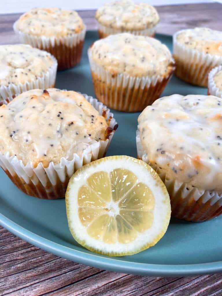 lemon poppy seed muffins sit on a light green plate.