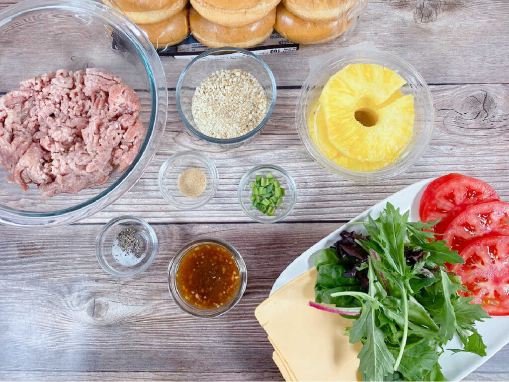 Ingredients for pineapple teriyaki burgers sit on a wooden background.