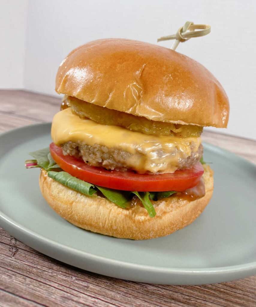 close up image of the burger on a light green plate. From the bottom up: lettuce, tomato, burger, grilled pineapple. Bun held together with a skewer.