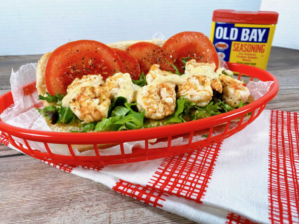 Steamed Shrimp Po Boy sandwich sits in a red basket on a checkered napkin. Shrimp are drizzled with Old Bay Remoulade sauce.