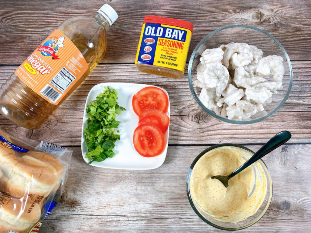 Ingredients for the sandwich sit on a wooden background - shrimp, old bay seasoning, lettuce, tomato slices, rolls, apple cider vinegar and the prepared remoulade.