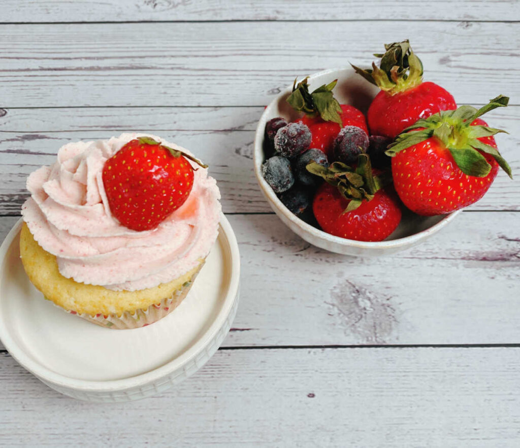 Overhead image of cupcake topped with a strawberry on a cupcake stand. Bowl of strawberries and blueberries is to the right of the cupcake.