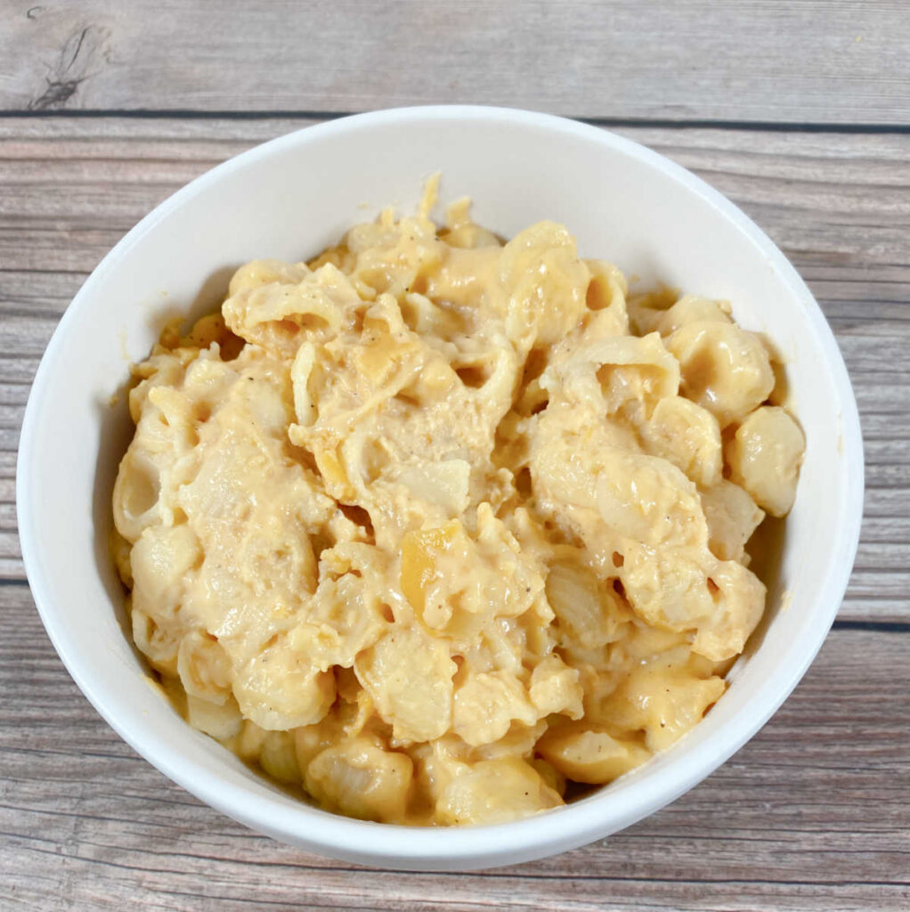 white bowl full of macaroni and cheese sits on a wooden background
