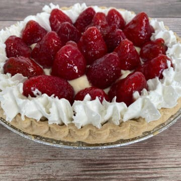 no-bake pie filled with pudding and topped with glaze strawberries and whipped cream sits on a wooden background