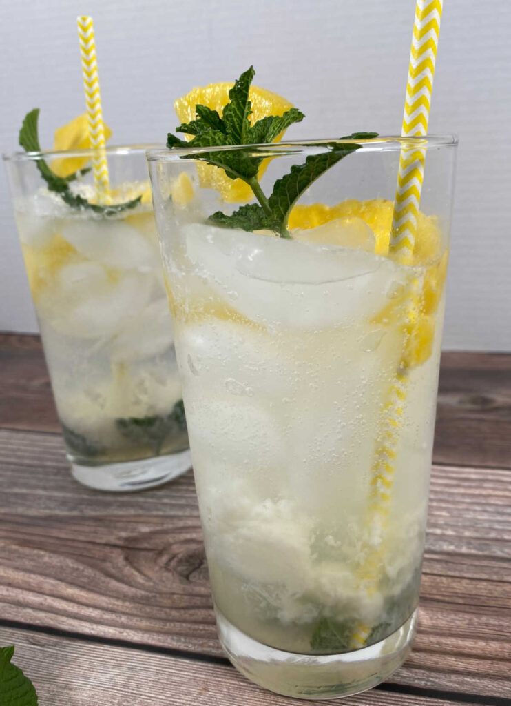 close up image of the cocktails, garnished with fresh pineapple, mint leaves and yellow straws