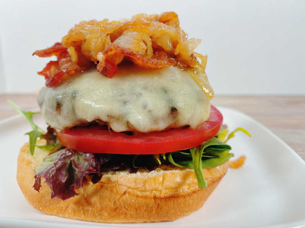 Open faced burger, showcasing the melty cheese, bacon and pile of caramelized onions sits on a white, square plate.
