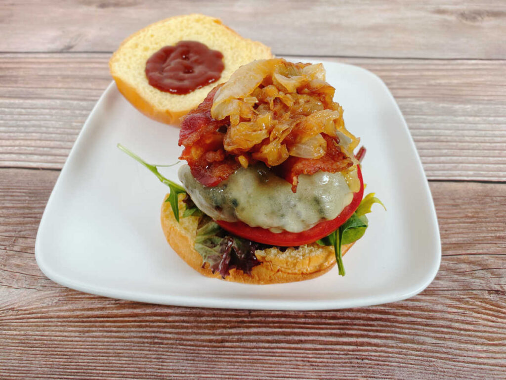 Burger, piled high with caramelized onions sits open faced on a white plate.