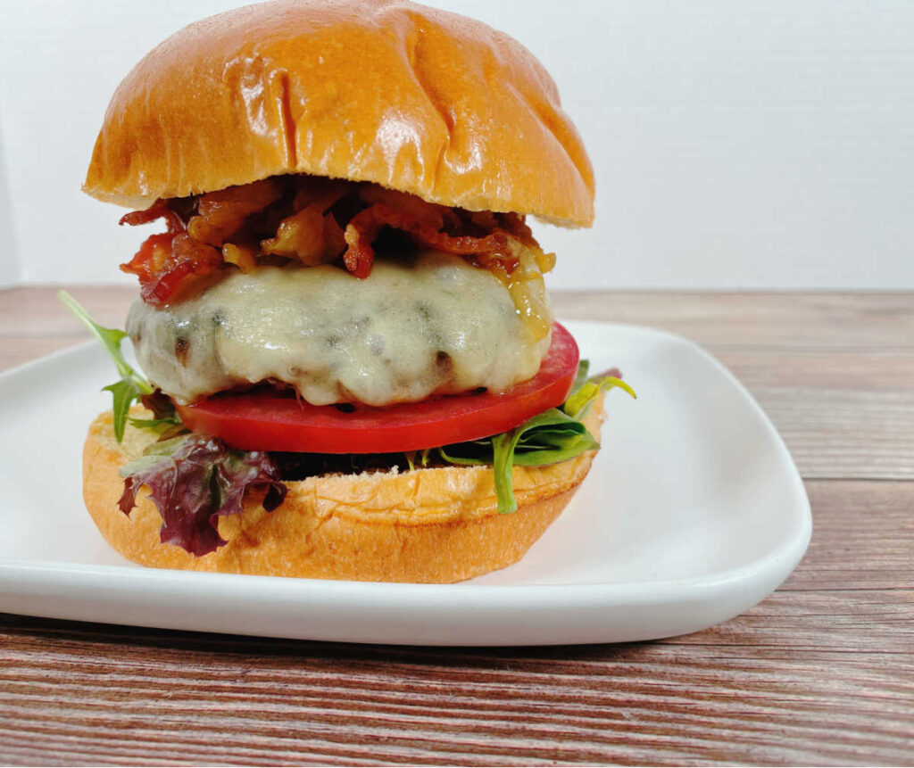 Assembled burger sits on a square white plate on a dark wooden background