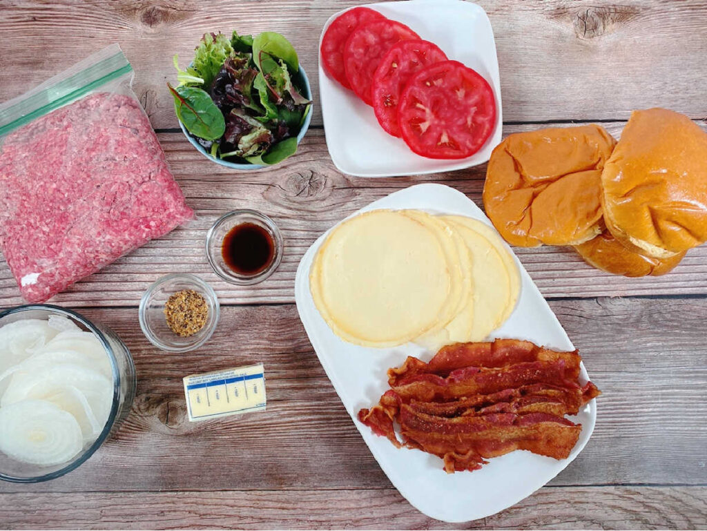 ingredients for the burger sit on a wooden background