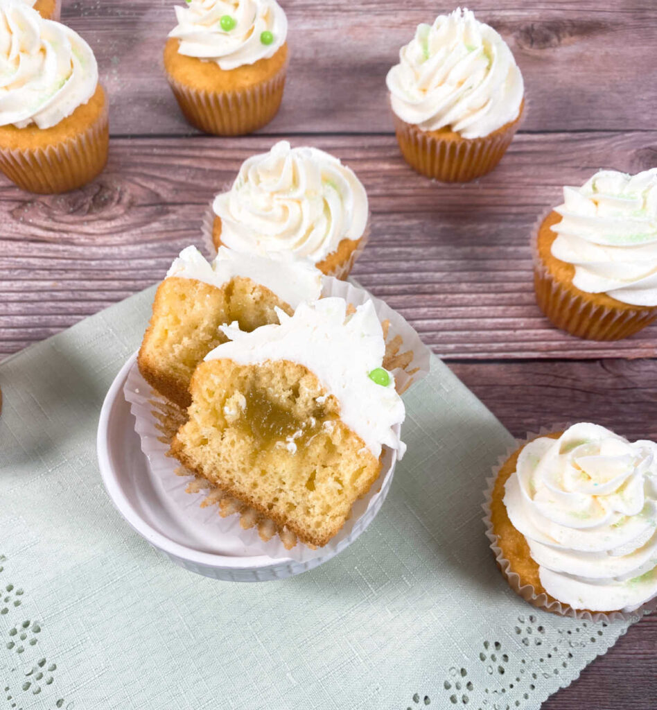 cupcake cut in half to show lime curd filling sits on a light green napkin. other decorated cupcakes surround it.